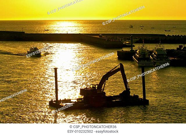 excavator machine construct on sea under twilight