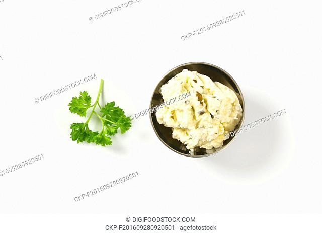 bowl of homemade cheese spread with herbs on white background
