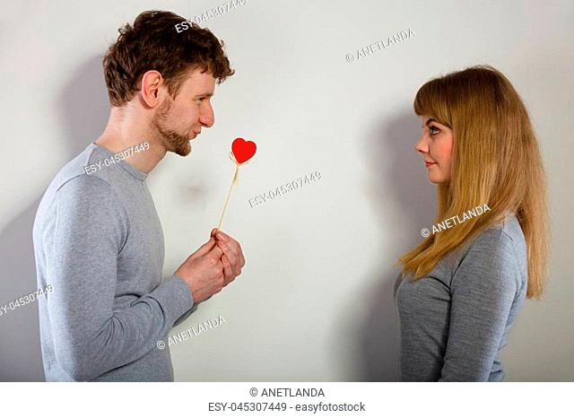 Romance symbolism valentines concept. Man giving heart to his girl. Young male proffesing love to woman, by giving her heart