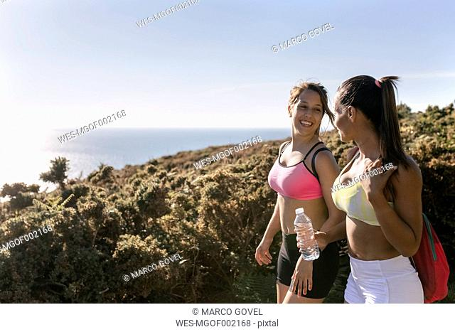 Spain, Asturias, two sportswomen, water bottle, smiling