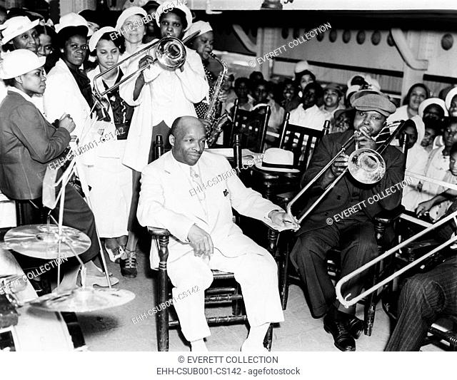 Father Divine is serenaded by followers on the steamer, Aug. 8, 1937. He is bound for his cult's 'Promised Land Olympic Games,' in Kingston, N.Y