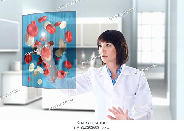 Mixed race doctor using digital display in doctor's office