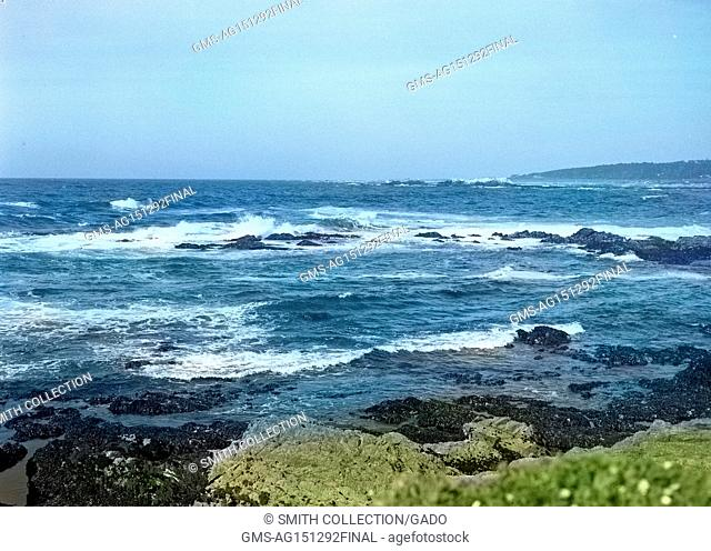 Waves break on rugged volcanic rocks on the coastline near Monterey, California, 1950. Note: Image has been digitally colorized using a modern process