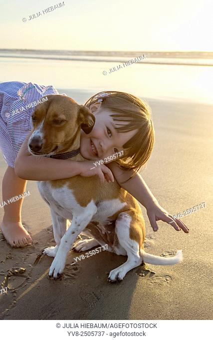 Toddler girl embracing her dog at the beach, La Jolla, California