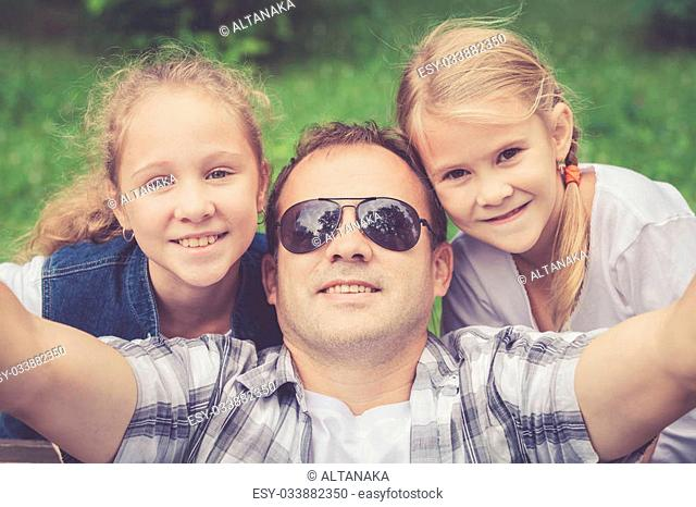 Father and daughters playing at the park at the day time. Concept of friendly family