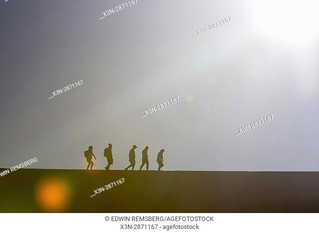 Tourists walking along the top of an ancient sand dune while the sun is setting in the Soussuvlei salt pan in Namib-Naukluft National Park, located in Namibia