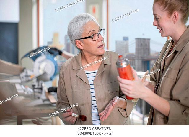 Mature female carpenter explaining wood stain to trainee in furniture making workshop