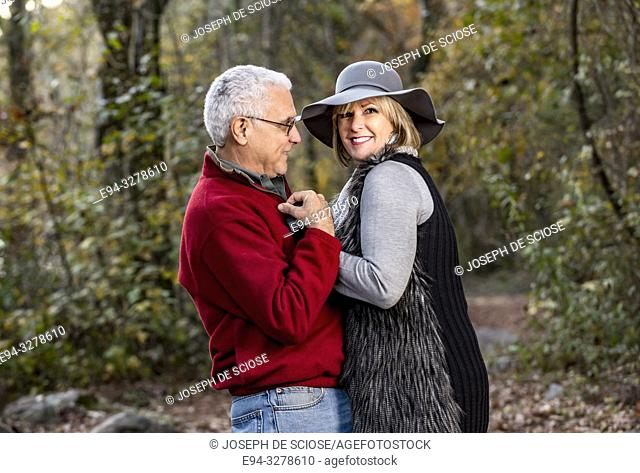 A happy 65 year old man and a 59 year old blond woman walking together in a forest setting