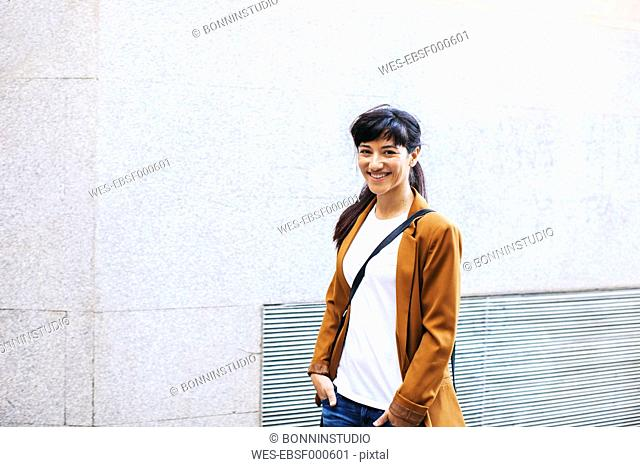 Smiling businesswoman in front of facade