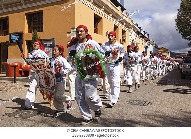 Pilgrims running in the street at the city centre during the celebration of the feast of Virgen de Guadalupe, San Cristobal De Las Casas, Chiapas Region, Mexico