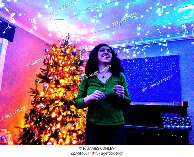 A woman decorates a room with holiday lights