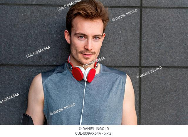Portrait of young man, wearing headphones around neck