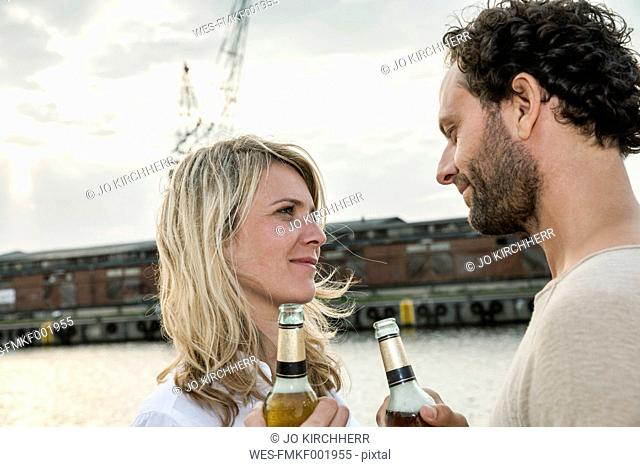 Couple drinking beer at the waterside