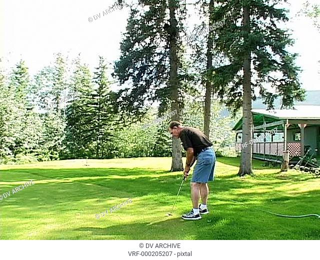 A golfer putts the ball while the camera zooms into a bear in a tree!