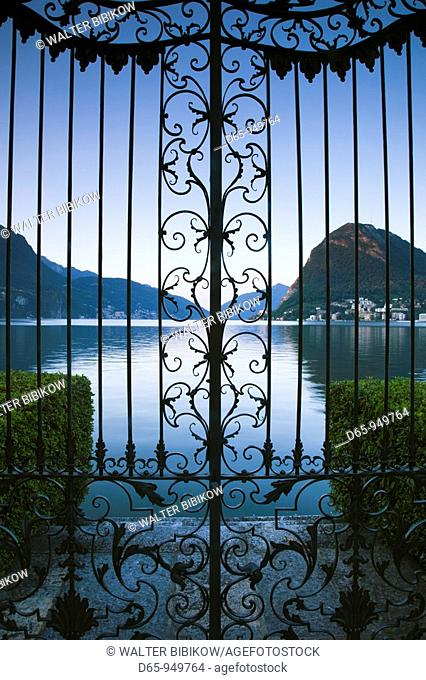 Switzerland, Ticino, Lake Lugano, Lugano, Parco Civico gate view of Monte San Salvador, dawn