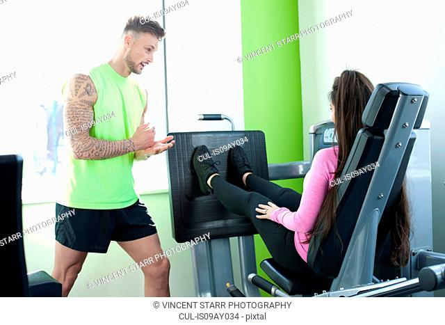 Personal trainer in gym instructing client using exercise machine
