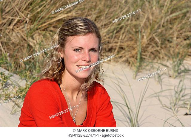 Portrait of a young blonde woman outdoors by sand dune at the beach