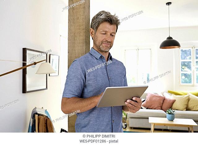 Mature man at home using digital tablet
