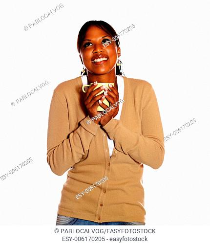 Attractive young woman holding a mug while looking up against white background