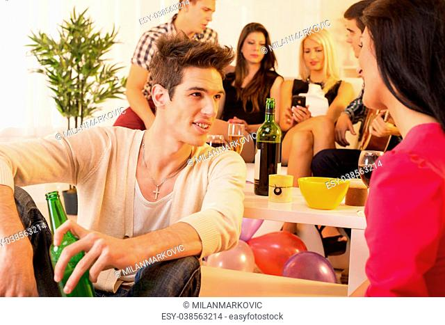 A group of young people in house party. In the first plan is handsome young man sitting on the floor, talking to a girl, and in the background a group of young...