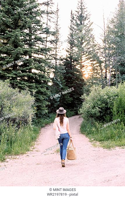 Woman walking along a forest path, carrying a bag