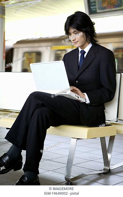 Businessman sitting on bench of train platform, using laptop