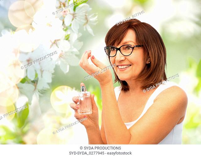 senior woman smelling perfume from her wrist