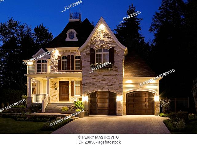 Illuminated, luxurious home with two car garage, landscaped front yard and paving stone driveway at dusk, Blainville, Quebec