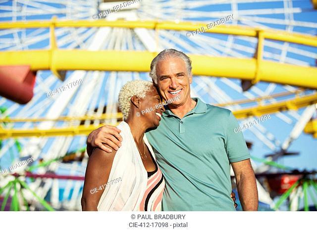 Portrait of hugging senior couple at amusement park
