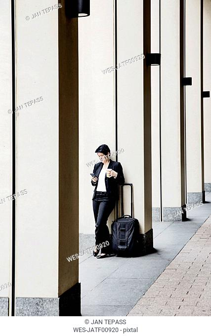 Businesswoman with trolley using smart phone, while drinking coffee