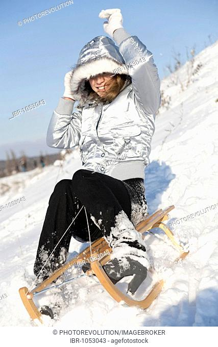 Young woman on a sledge in snow