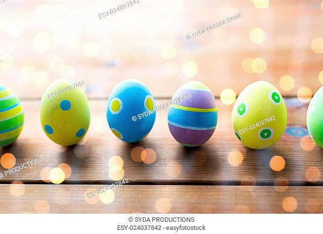 easter, holidays, tradition and object concept - close up of colored easter eggs on wooden surface over holidays lights