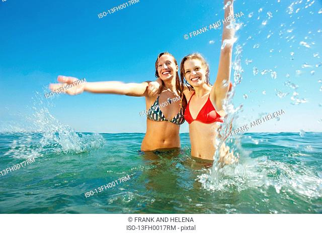 Two girls splashing in the sea