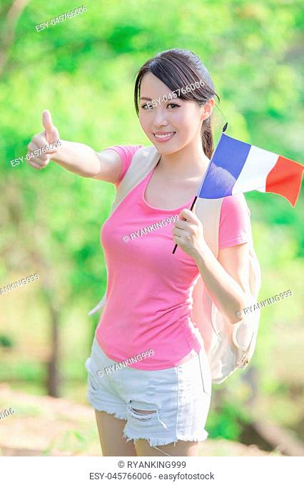 happy college student girl hold french flag and show thumb up with nature white background, asian