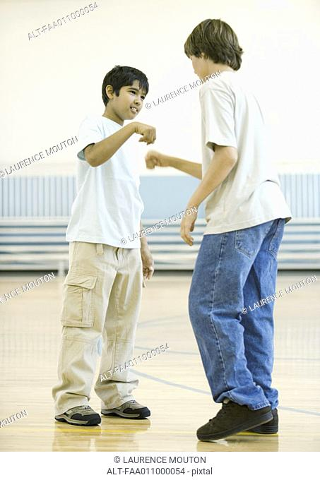 Two teen boys performing special handshake in school gym