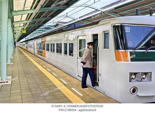 Engineer boards local train in Izu Peninsula, Japan. JR: Japan Railroad
