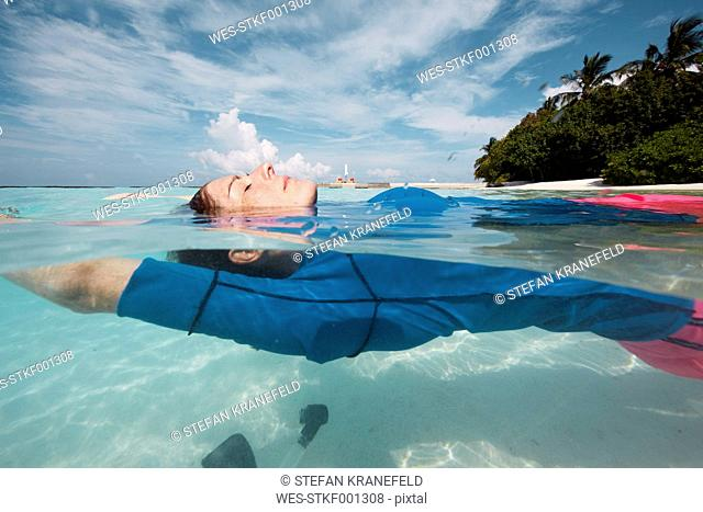 Maldives, woman floating on water in the Indian Ocean