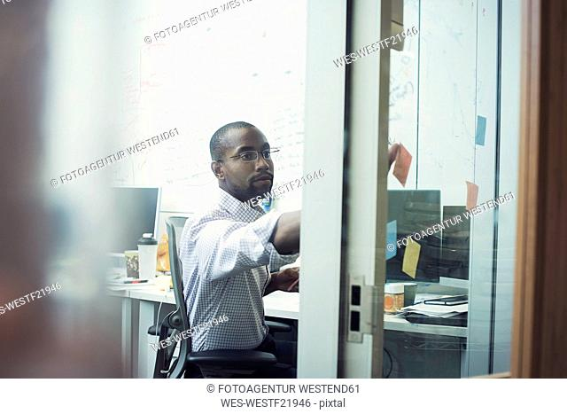 White collar worker sitting in office, sticking notes on glass walll