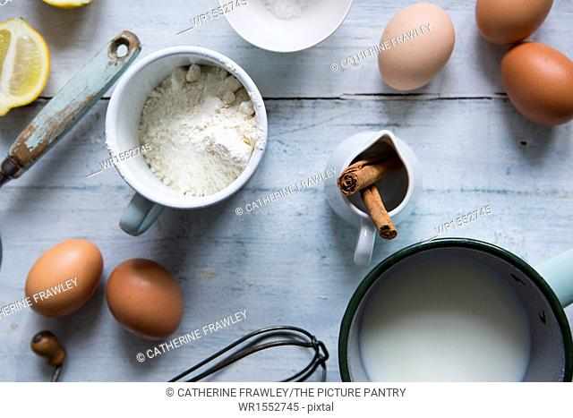 Ingredients for making pancakes, including eggs, flour cinnamon and a whisk