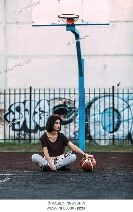 Young woman sitting with basketball on outdoor court