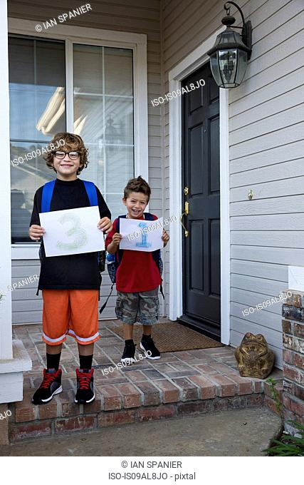 Portrait of two brothers holding up pieces of paper with 3 & 1