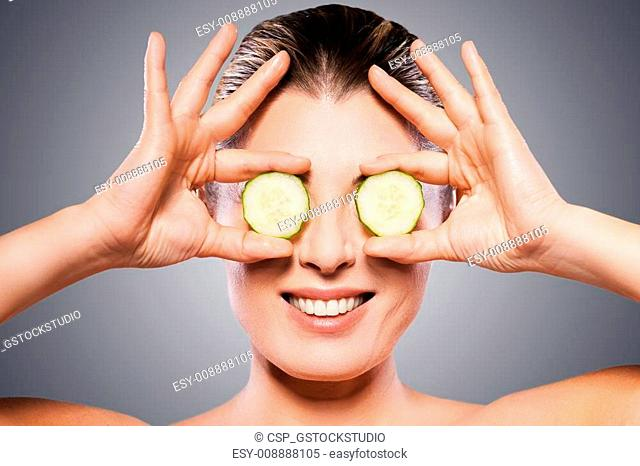 Natural spa treatment. Cheerful mature woman holding pieces of cucumber in front of her eyes while standing isolated on white background