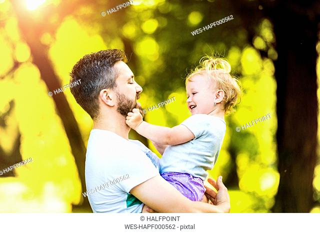 Father holding little daughter on his arms