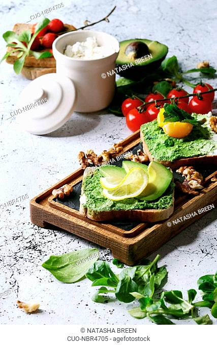 Vegetarian sandwiches with avocado, ricotta, egg yolk, spinach, cherry tomatoes on whole grain toast bread on wooden slate board with ingredients above over...