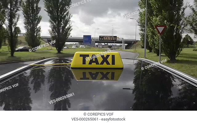 Car with a taxi sign on its roof driving over a motorway and through a city, seen from the roof of the car, towards a residential neighborhood