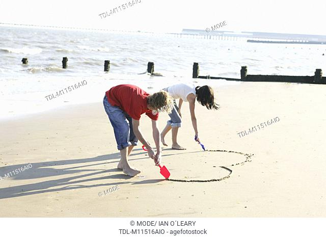 A young couple drawing a heart shape in the sand