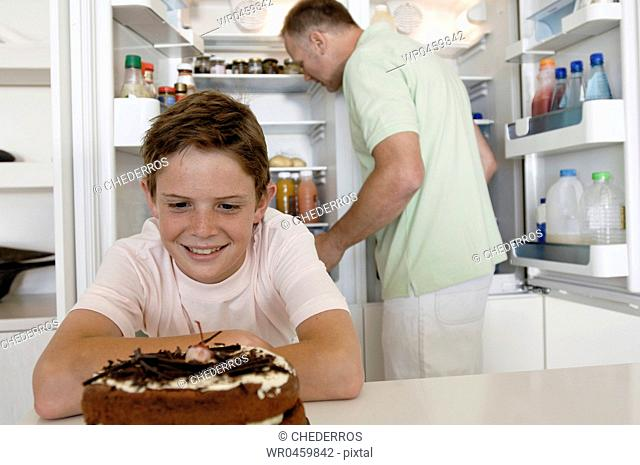 Close-up of a boy looking at a cake with his father standing behind him in front of an open refrigerator