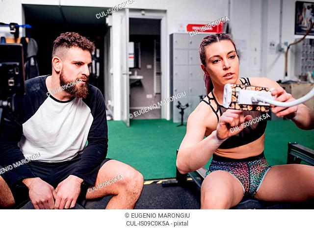 Young woman and man training together, setting rowing machine controls in gym