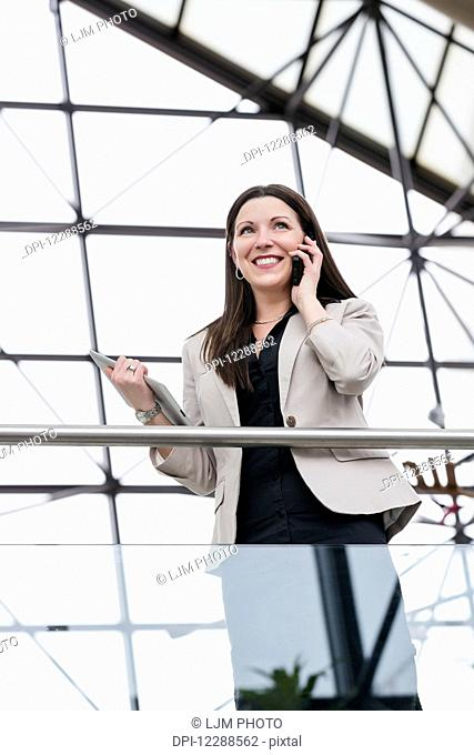 Mature business woman talking on her smart phone and holding a tablet in the atrium of an office building; Edmonton, Alberta, Canada