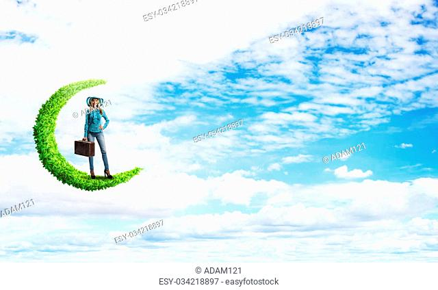Beautiful woman traveler in hat with suitcase on green moon